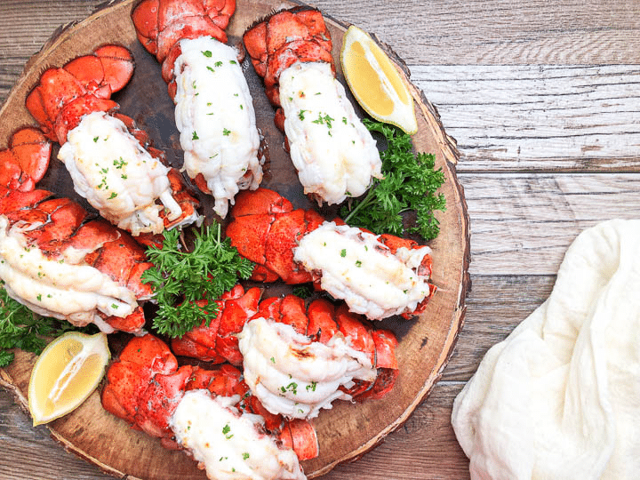 lobster tails on wooden tray with lemon wedges