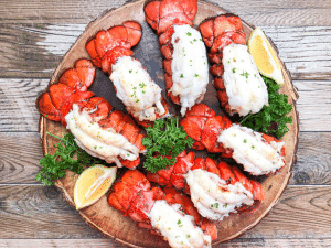broiled lobster tails on round serving platter garnished with parsley