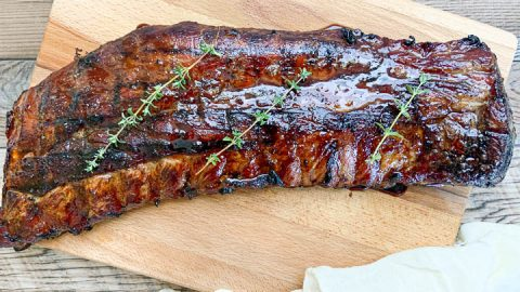 grilled teriyaki pork ribs on cutting board garnished with thyme