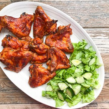 bbq chicken wings on white platter with green salad