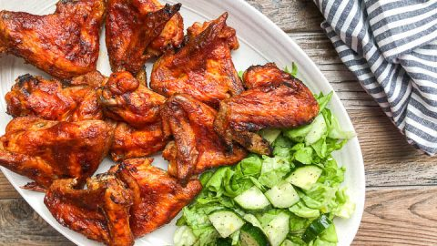 close up photo of bbq chicken wings on oval platter