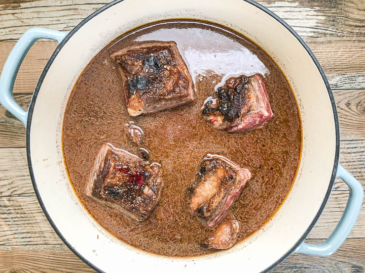 seared short ribs in red wine and chicken broth in dutch oven