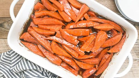 candied yams in white casserole dish next to gray striped napkin