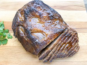 braised brisket cut into slices on cutting board