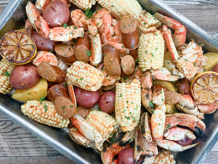 seafood boil in pan garnished with lemon lemon and parsley