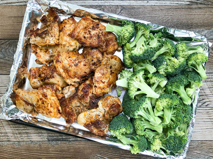 seared chicken thighs and cut broccoli florets on sheet pan
