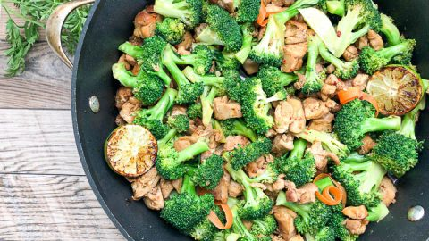 overhead shot of chicken and broccoli with parsley near skillet