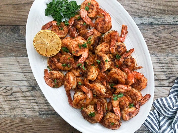 seared cajun shrimp on platter garnished with lemon and parsley