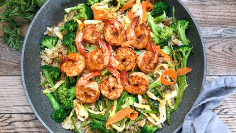 vegetable fried rice topped with seared shrimp