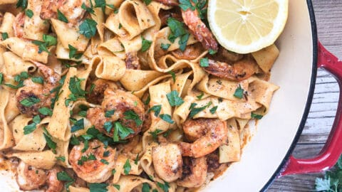close-up of cajun shrimp pasta with slice of lemon in dutch oven