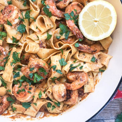 close-up of cajun shrimp pasta with slice of lemon in dutch oven