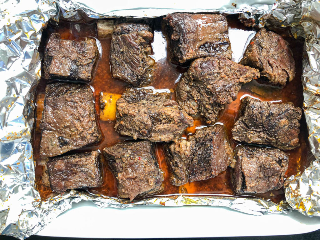 foil unwrapped showing beef short ribs after being cooked for several hours