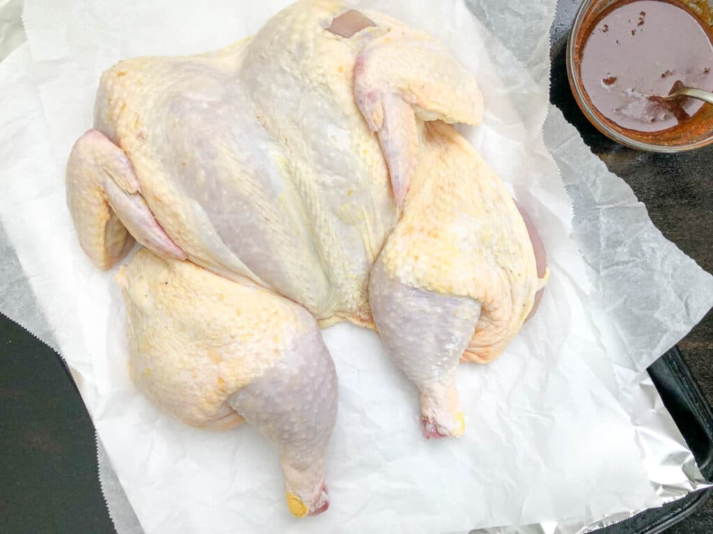 raw spatchcock chicken on parchment paper