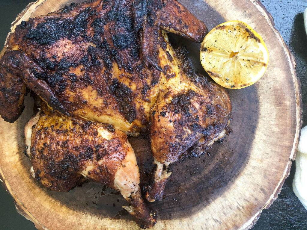 grilled chicken on platter next to grilled lemon.