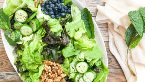 spring mix salad on platter with beige napkin next to platter