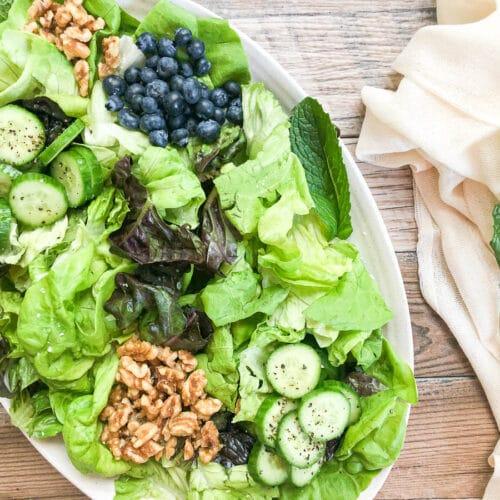 spring mix salad on platter with beige napkin next to platter