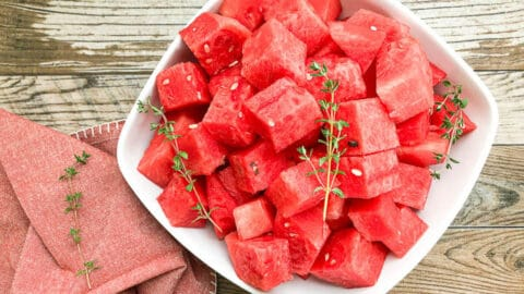 watermelon cut into cubes in white bowl with garnish