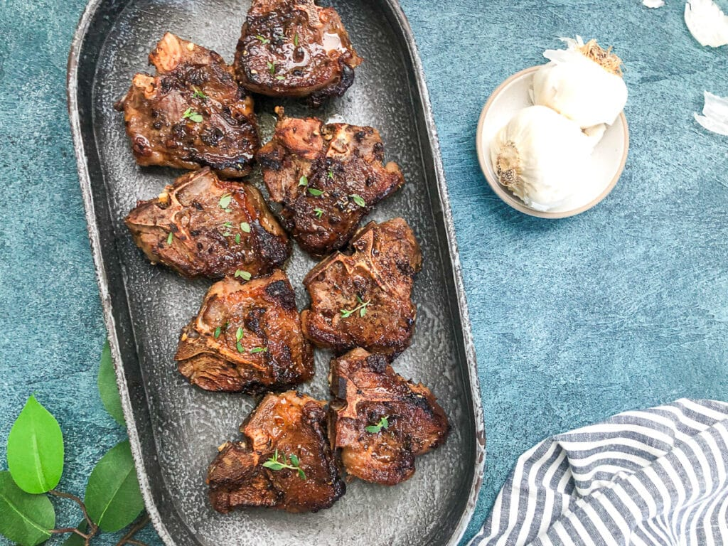lamb loin chops in gray platter with striped napkin on side