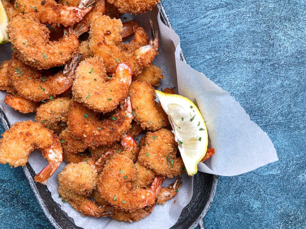 close up image of panko fried shrimp with lemon garnish.