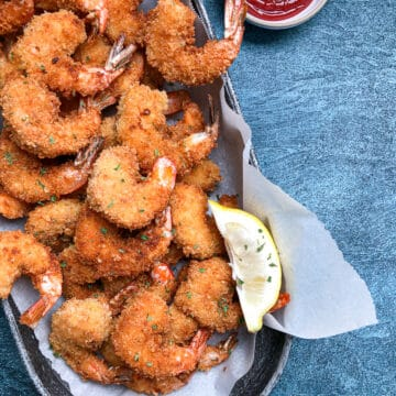 panko fried shrimp in oval platter with dipping sauce.
