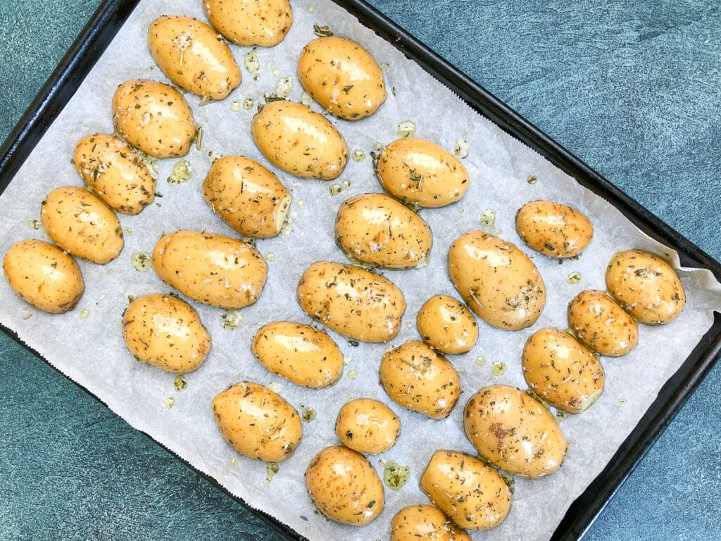 yellow dutch baby potatoes cut in half on baking sheet
