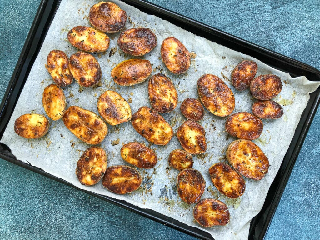 crispy oven roasted baby potatoes flipped over on baking sheet