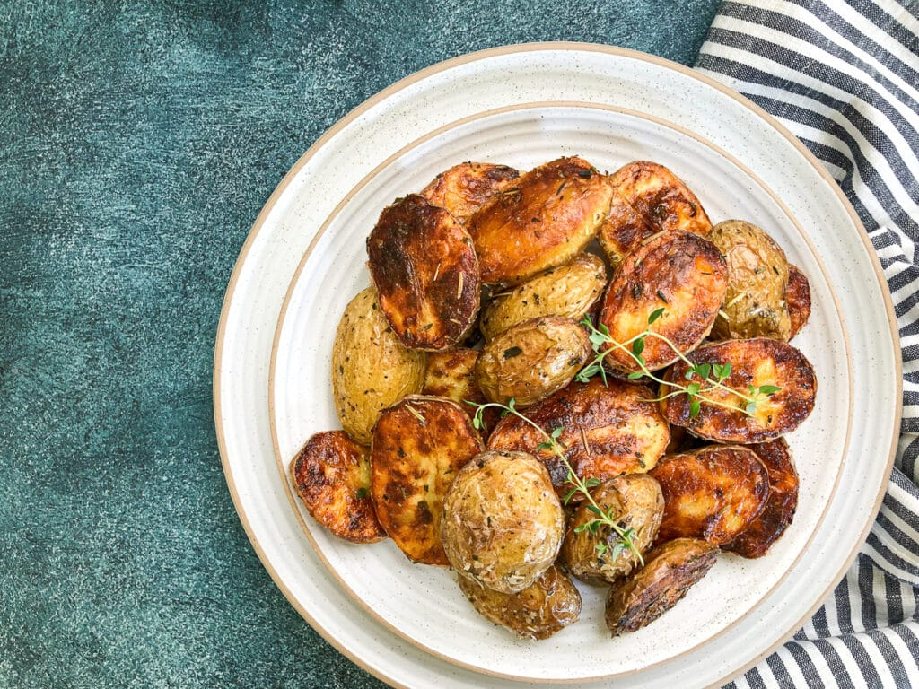 crispy oven roasted baby potatoes on white plate with striped napkin next to plate