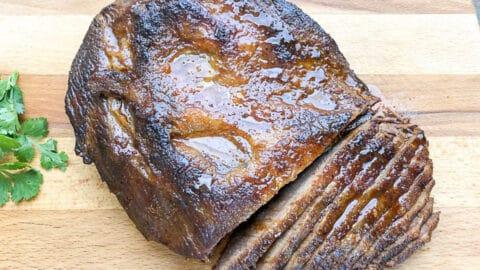 sliced braised brisket on wooden cutting board