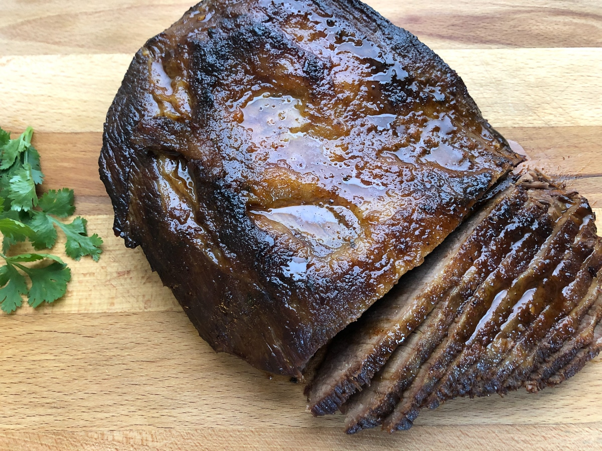 braised brisket partially sliced on cutting board